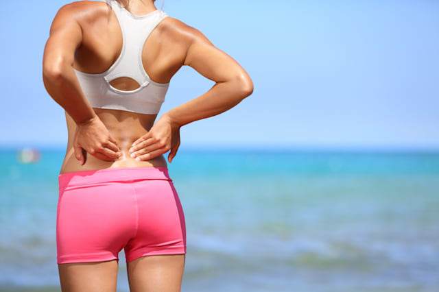 Back pain. Athletic woman in pink sportswear standing at the seaside rubbing the muscles of her lower back, cropped torso portra