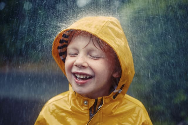 Happy smiling little boy in the rain