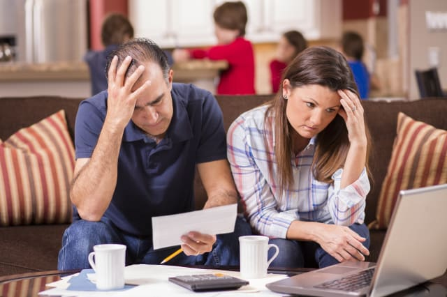 Latin descent man and woman struggle to pay their monthly bills.  They are calculating expenses versus budget income and are ups