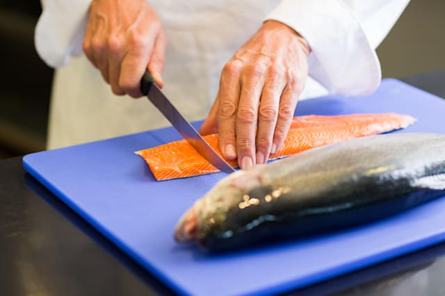 Closeup mid section of a chef cutting fish