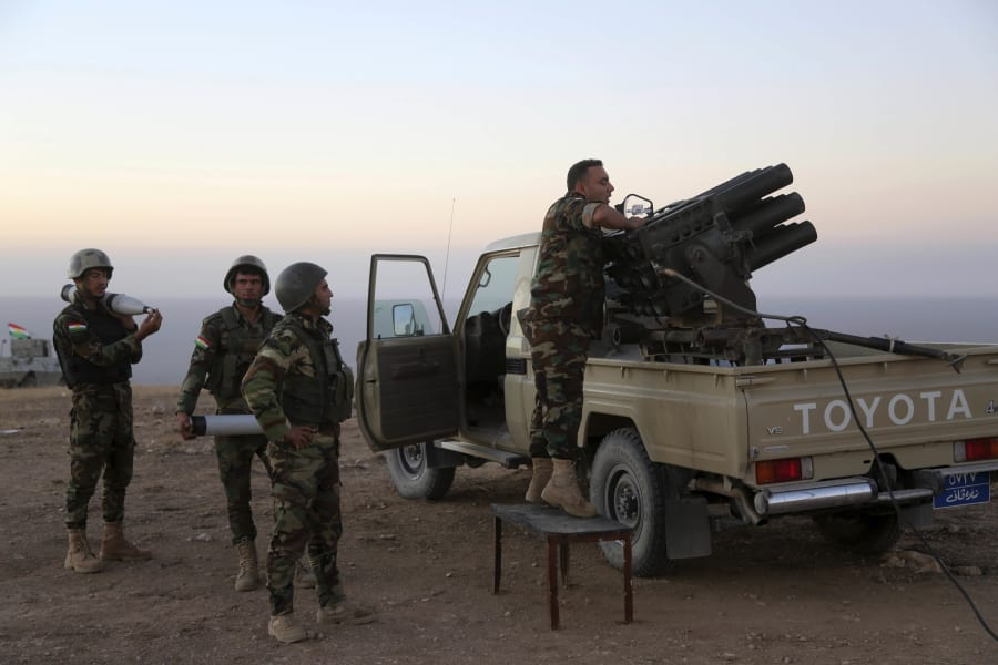 Kurdish security forces take up a position as they fight overlooking the Islamic State-controlled in...