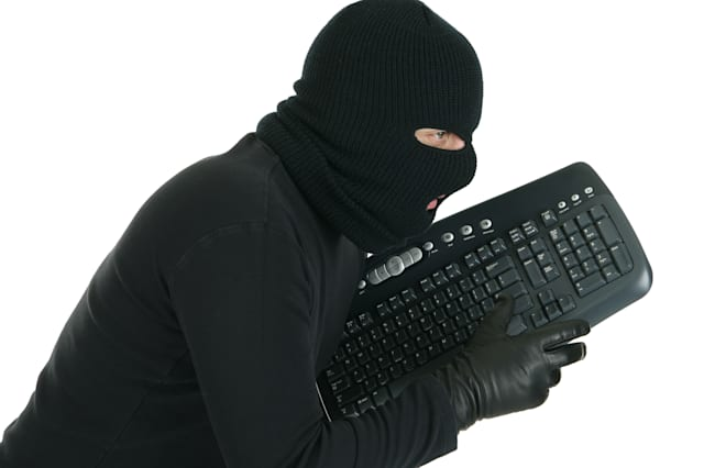 Computer hacker -  masked criminal with keyboard