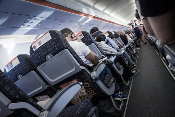 Onboard an EasyJet flight, bound for Spain, showing the flight attendant walking the aisle.