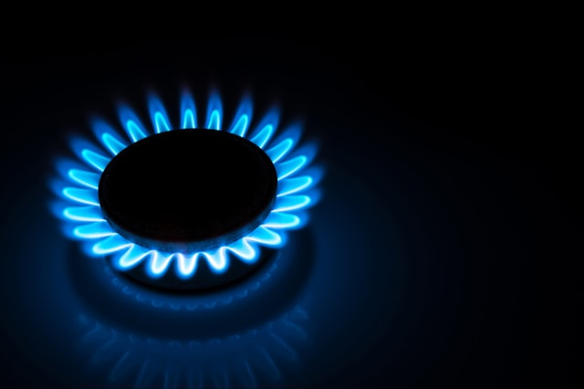 burning gas stove hob blue flames close up in the dark on a black background