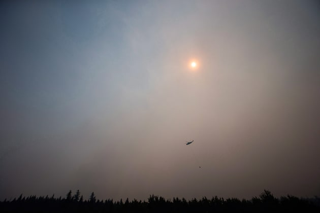 Smoke obscures the sun as a helicopter carrying a bucket battles the Gustafsen wildfire near 100 Mile...