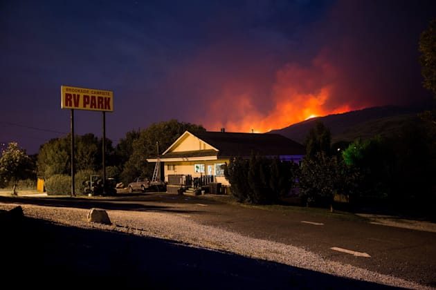A wildfire burns on a mountain behind an RV park office in Cache Creek, B.C. in the early morning hours...