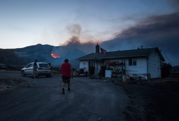 Darin Minnabarriet walks to his house that survived a wildfire on the Ashcroft First Nation, as a fire...