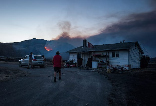 Darin Minnabarriet walks to his house that survived a wildfire to empty his freezer on the Ashcroft First...