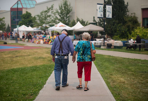 Wildfire evacuees McLean Rislund, 80, and June Rislund, 81, from Forest Grove near 100 Mile House, walk...