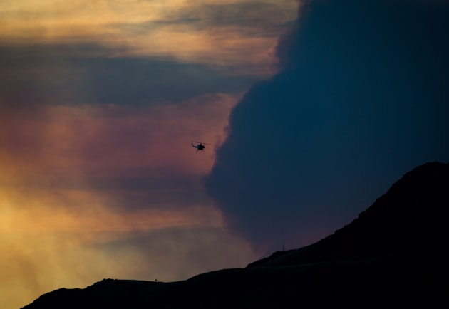 A firefighting helicopter flies past smoke in the air from a wildfire burning near Ashcroft, B.C. at...