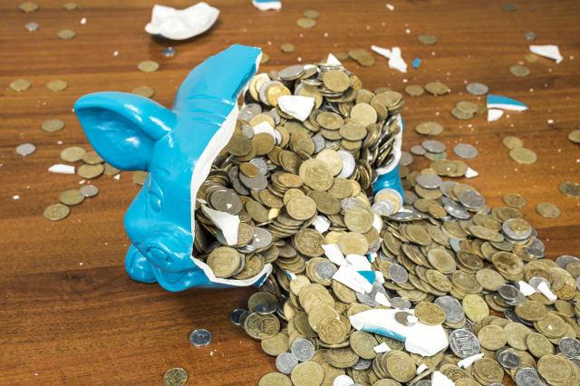broken piggy bank with coins. ...