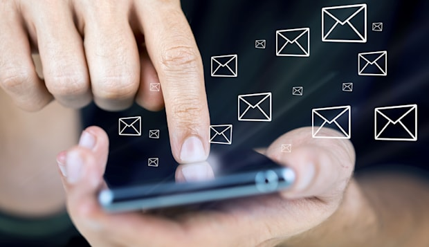 Closeup of using modern mobile phone with email icons around it.