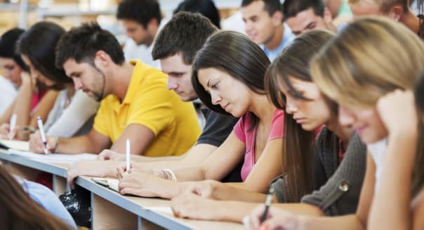'Group of college students in the university amphitheatre, they are sitting and doing an exam. The focus is on the brunette in p