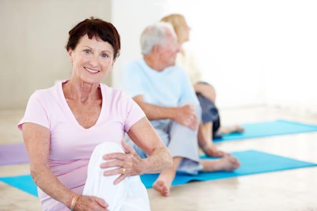 Portrait of a senior woman enjoying a yoga class with other seniors