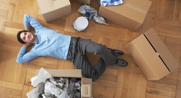 B8JNNT Man resting amongst cardboard boxes