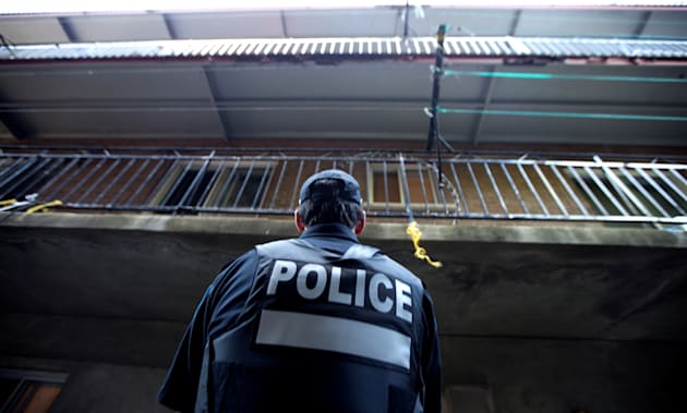 A police officer stands in the back alley of the home of Amor Ftouhi, in Montreal on Wednesday. Ftouhi...