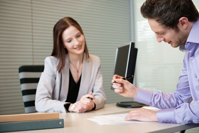 BP6MH2 Man signing documents with a female real estate agent sitting in front of him  man; signing; documents; agreement; woman;