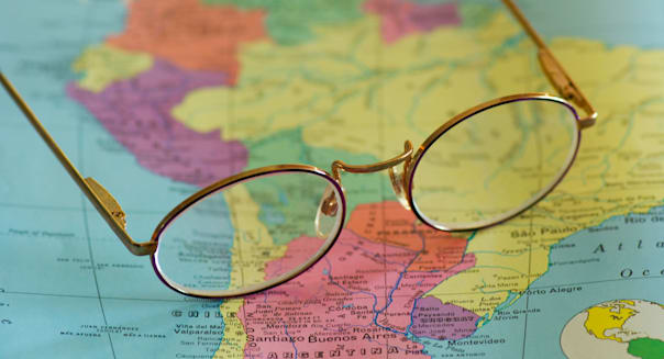 closeup of reading glasses on map of South America