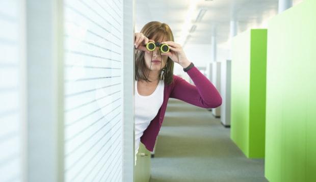 Businesswoman looking through binoculars in an office corridor