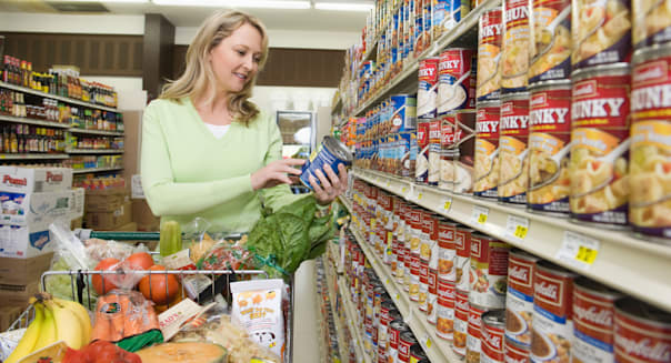 BH1YMJ Mature woman selects tinned goods in supermarket aisle. Image shot 2009. Exact date unknown.