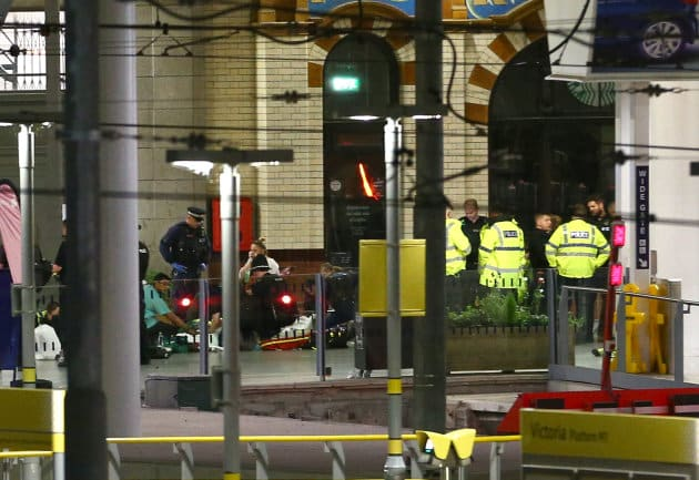 Paramedics treat the injured outside Victoria Station, directly below the arena. The station has been...