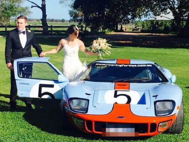 Adam Cranston posing in front of the car with his wife Elizabeth on the couple's wedding day. There is...