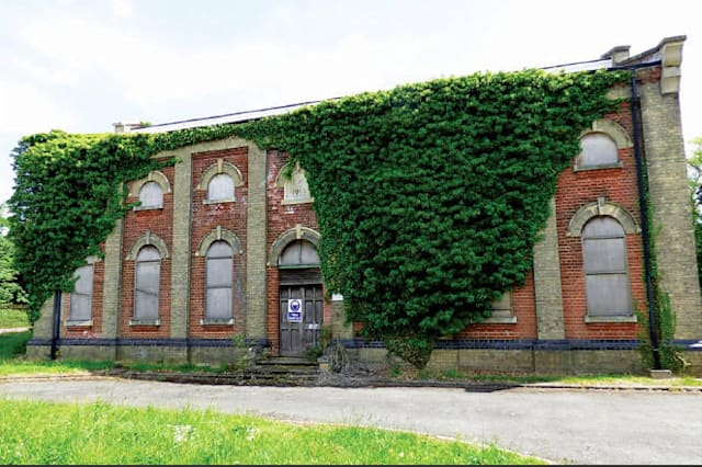 The front of the ivy-covered old pump house