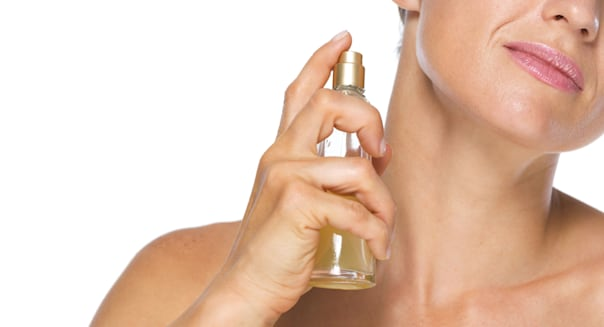 Closeup on young woman applying perfume