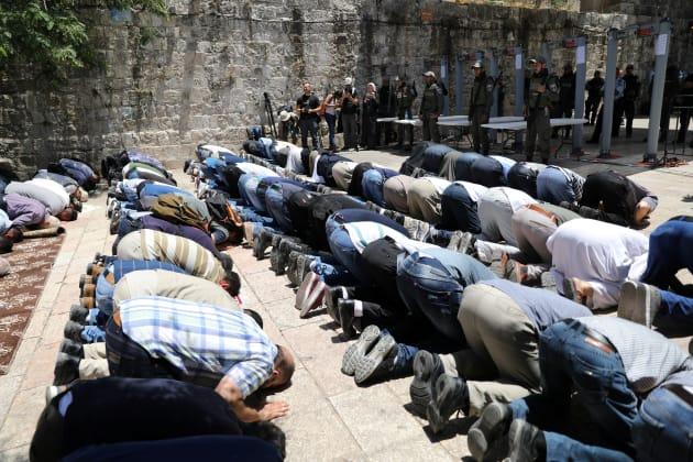Des Palestiniens prient devant des policiers israéliens et les nouveaux portiques de sécurité, le 16...