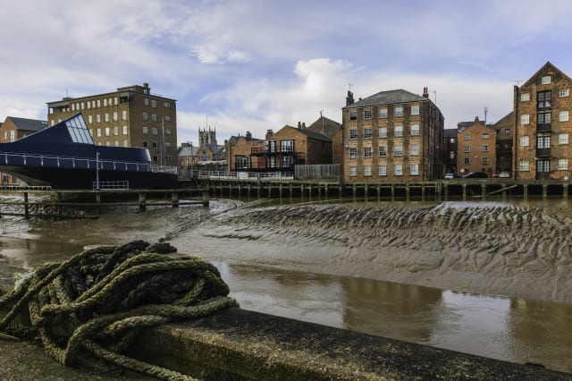 River Hull with bridge, flats, and church on the horizon.