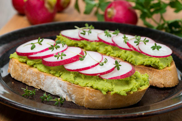 toasted ciabatta with pate of avocado and fresh radish, close-up, horizontal