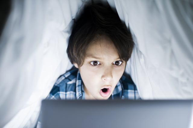 Boy using computer under blanket at night