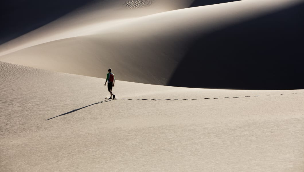 A man walking through the vast landscapes in Sand Dunes National Park in Alamosa, Colorado.
