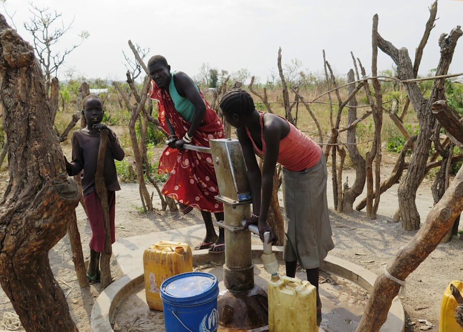 Children pump water from a borehole drilled by Plan International at Melijo
