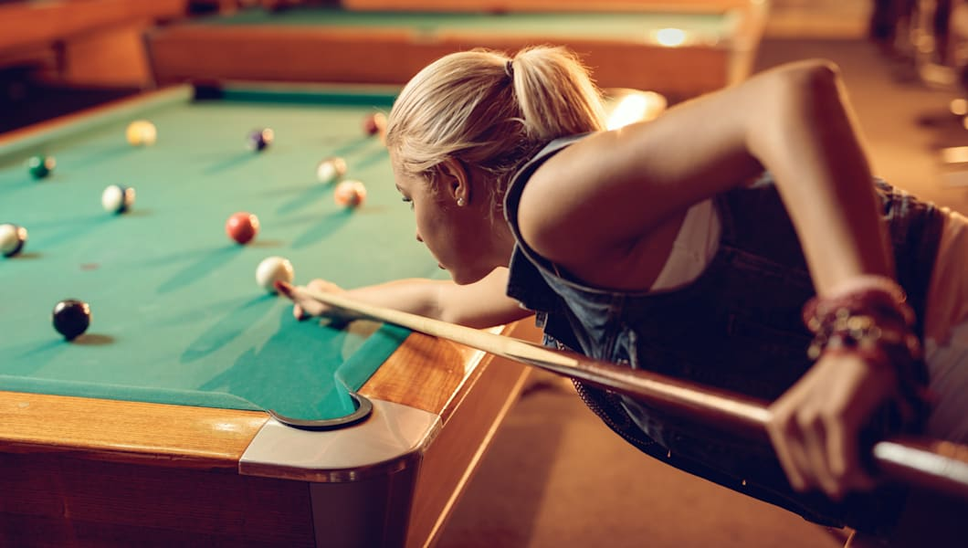 Beautiful woman concentrating while aiming at pool ball.
