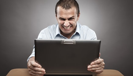 C6XRE1 Portrait of an angry businessman at his laptop, on gray background