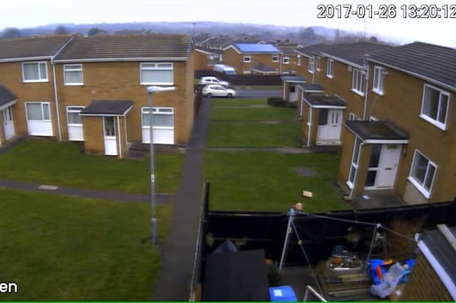 CCTV from the garden showing the Hermes delivery driver throw the parcel over the garden fencce in Chester-le-Street, County Durham. See Masons copy MNHERMES: A Hermes courier launched a customer's £50 delivery over a back garden fence without even checking if anyone was home first. The shocking moment was caught on CCTV as the man can be seen launching the small parcel the entire length of the 20ft garden. Customer Kaitlin Mitchinson, 19, had spent £41 on an eyeshadow palette which ending up landing at the back door. In the footage, captured last Thursday (26/01), the man can be seen jogging towards the back garden and heading towards the front of the house.