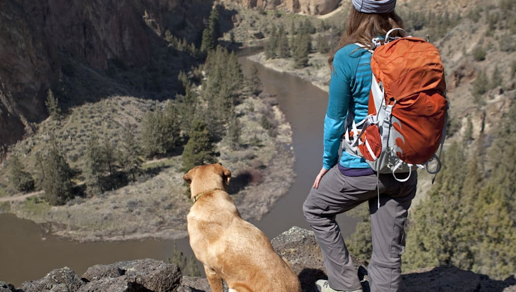 A woman and her dog standing on a cliff overlooking Smith Rock and the Crooked River below.