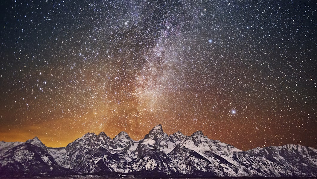 Milky Way over Grand Teton. The city light behind Teton mountains cast an orange glow. All comments or critiques are greatly appreciated!