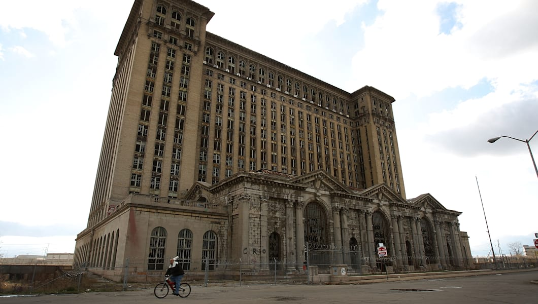 DETROIT - NOVEMBER 20: A man rides his bike past the shuttered Michigan Central Railroad Station November 20, 2008 in Detroit, Michigan. An estimated one in three Detroiters lives in poverty, making the city the poorest large city in America.  The Big Three U.S. automakers, General Motors, Ford and Chrysler, are appearing this week in Washington to ask for federal funds to curb to decline of the American auto industry. Detroit, home to the big three, would be hardest hit if the government lets the auto makers fall into bankruptcy.  (Photo by Spencer Platt/Getty Images)