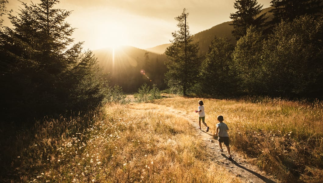 Kids running towards the sun in Olympic National Park.