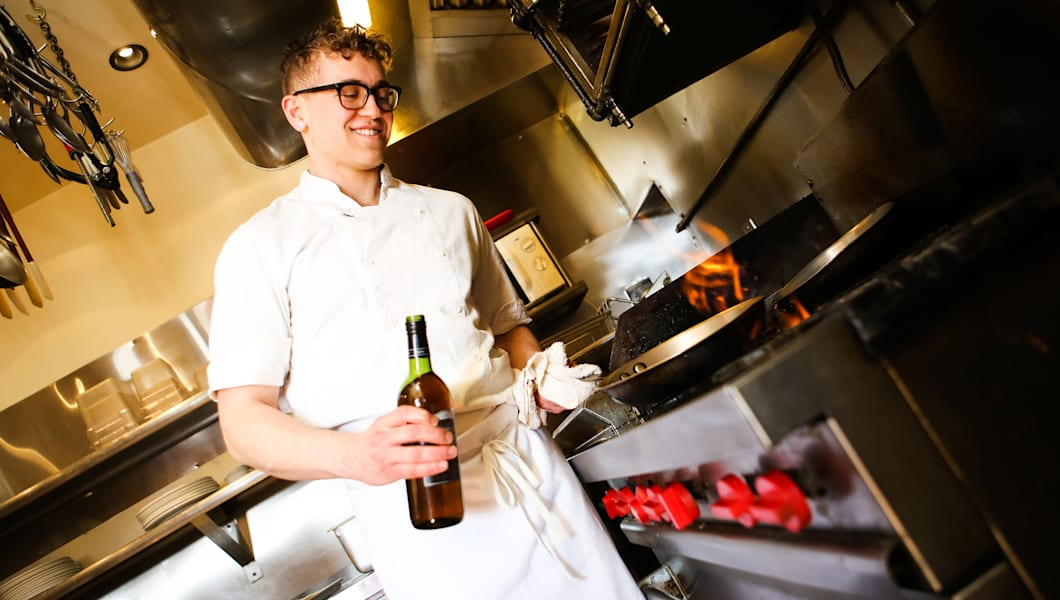 Cute young male chef cooking in a pan with sherry, in restaurant kitchen.