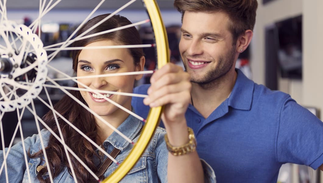 Close up of happy young woman holding a bicycle wheel in bike store with her boyfriend or sales clerk standing behind her.
