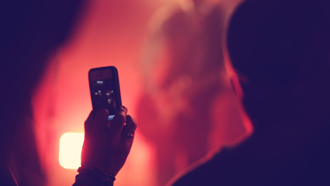 Someone holding a phone at a  live music event taking a photo on an iphone