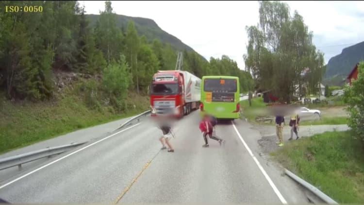 Dash-cam video shows near miss between semi, child