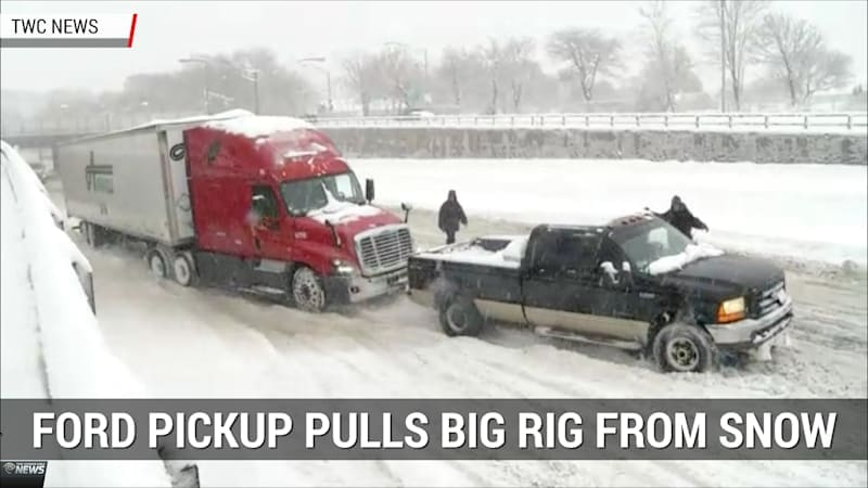 Ford pickup tows semi trucks out of snow bank during snowstorm