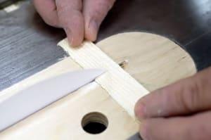Papier sägt Holz: Druckerpapier in die Kreissäge gespannt