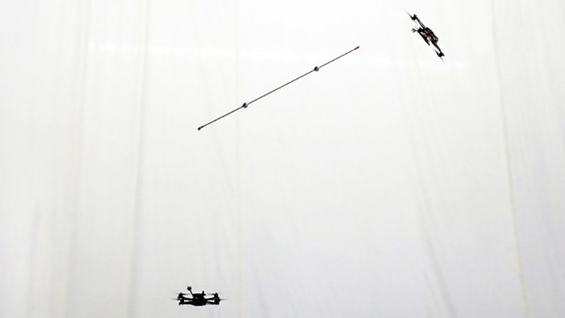Quadrocopters can balance, juggle poles in mid-air now (video)