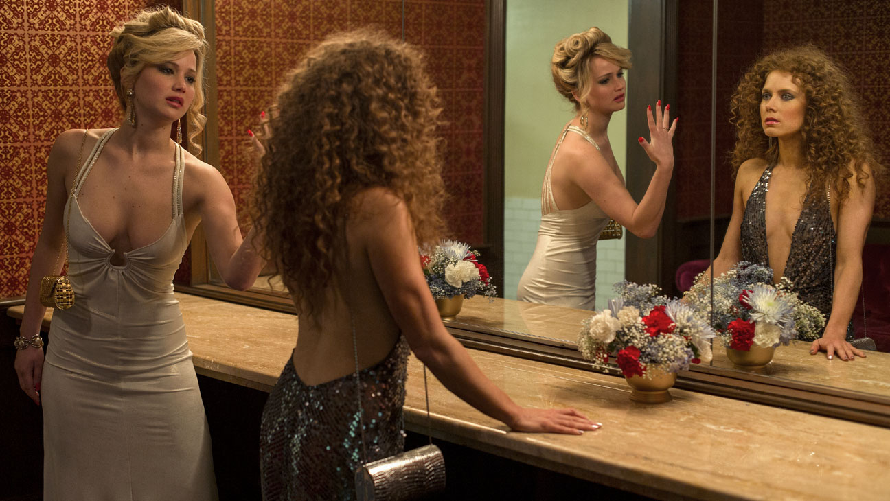 Rosalyn Rosenfeld (Jennifer Lawrence) & Sydney Prosser (Amy Adams) in the Grand Old AC Hotel powder room in Columbia Pictures' AMERICAN HUSTLE.