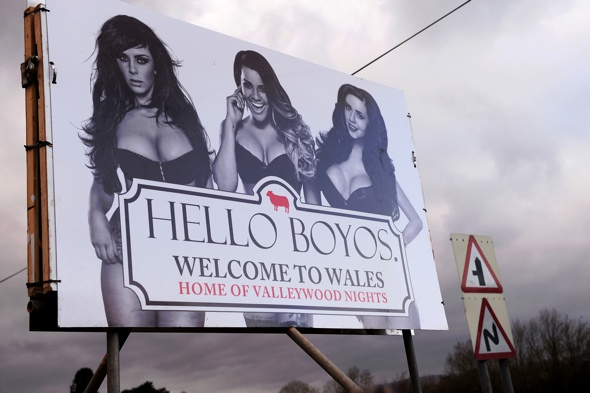 ***EXCLUSIVE - FREE FOR USE***  ABERGAVENNY, UNITED KINGDOM - FEBRUARY 23: A front view of an MTV pop-up billboard depicting The Valley TV Reality Stars Natalee Harris, Lateysha Grace and Jenna Jonathan on February 23, 2014 in Abergavenny, Wales.  A CHEEKY alternative ëWelcome to Walesí sign on the A465 Welsh border has been setting male commuterís hearts racing. The pop-up billboard, which was installed on Sunday morning (Feb 23), carries the phrase 'Hello Boyos' - a cheeky nod to the iconic Wonderbra ads of the mid 90s. Erected by MTV bosses to celebrate the third season of reality TV show The Valleys, which hits TV screens on Tuesday night at 10pm on MTV, the eye-popping sign features three of the showís biggest stars Natalee Harris, Lateysha Grace and Jenna Jonathan in racy underwear.  The striking design is being trialled on the A465 on the Welsh border, but is due to be rolled out at several crossings into Wales later this week in advance of the new series airing.  PHOTOGRAPH BY Dan Rowley / Barcroft Media  UK Office, London. T +44 845 370 2233 W www.barcroftmedia.com  USA Office, New York City. T +1 212 796 2458 W www.barcroftusa.com  Indian Office, Delhi. T +91 11 4053 2429 W www.barcroftindia.com